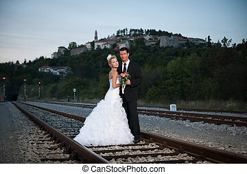 Bride and groom on a railway at dusk