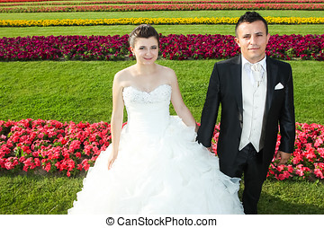 Bride and groom on lawn with flowers