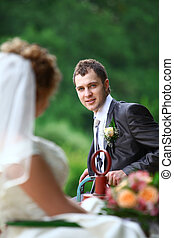Bride and groom on swing in summer forest