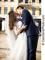 bride and groom passionately kissing on street at sunny day