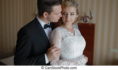 Bride and groom pose to photographer in a hotel room