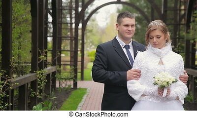Bride and groom pose to photographer outdoor