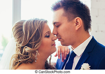 Bride and groom posing in a hotel room on background windows