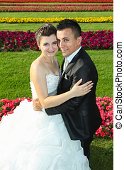 Bride and groom posing on lawn with flowers