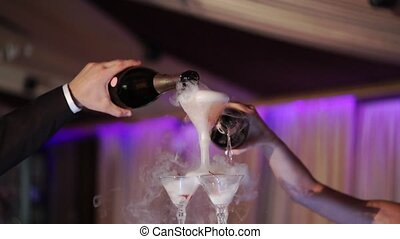 Bride and groom pouring wine to pyramid of glasses with champagne