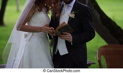 bride and groom reading a book outdoors