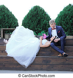 bride and groom resting on a wooden podium