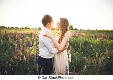 Bride and groom, rissing at sunset on a beautiful field with flowers, romantic married couple