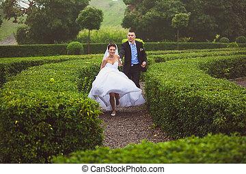 Bride and groom running at garden maze