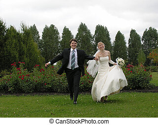 bride and groom running from trees