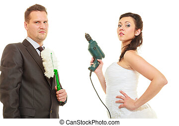 Taking care of house together, sharing household duties concept. Bride in wedding dress and groom wearing elegant suit holding cleaning equipment and tools.