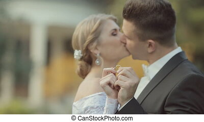 Bride and groom show their wedding rings, kiss and look into each other's eyes