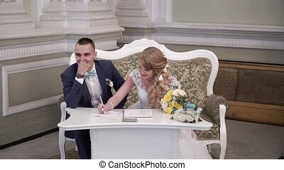 Bride and groom signing documents at wedding ceremony