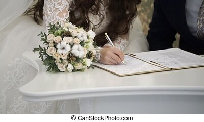 Bride and groom signing documents at ceremony