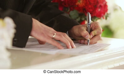 Bride and Groom Signing Marriage Certificate - The bride and...