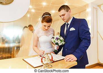 Bride and groom signing marriage license or wedding