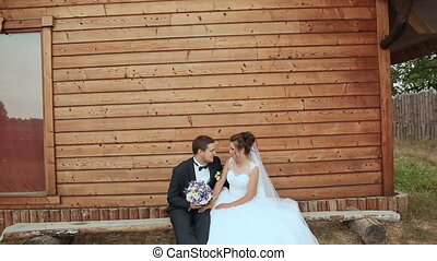 Bride and groom sit on a bench in the old house. Floating camera.