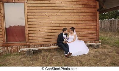 Bride and groom sit on a bench in the old house