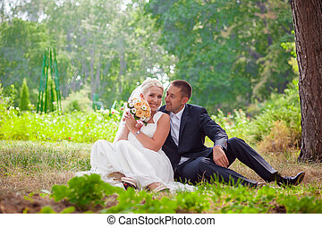 bride and groom sit on grass in the park