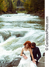 Bride and groom sit on the stones while a mountain river flows behind them