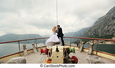 Bride and groom sitting at the stern of vintage yacht sailing on the sea in Montenegro, Budva