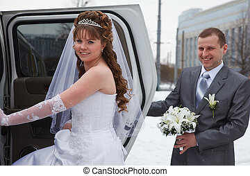 Bride and groom sitting in car