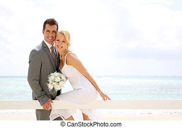 Bride and groom sitting on a fence by the beach