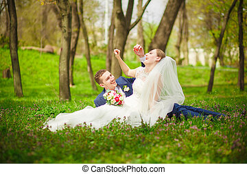 Bride and groom sitting on the grass