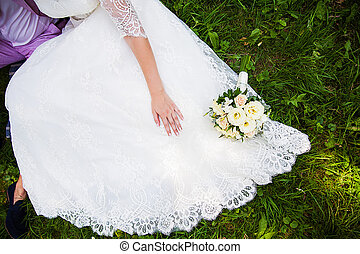 bride and groom sitting on the grass with beautiful bouquet