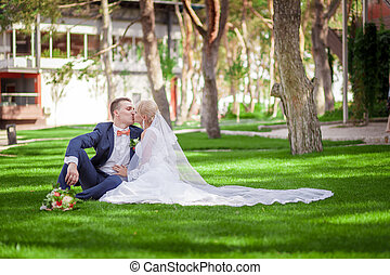 bride and groom sitting on the green grass