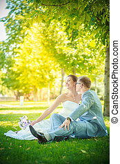 Bride and groom sitting on the lawn