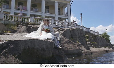 Bride and groom sitting on the rocks