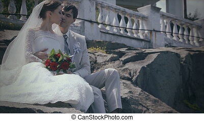 Bride and groom sitting on the rocks, love to cuddle