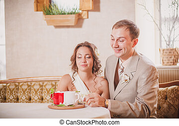 Bride and groom sitting on the table