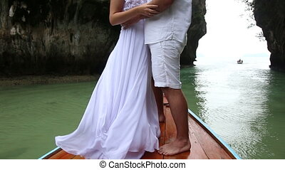 bride and groom stand and kiss on longtail wooden boat