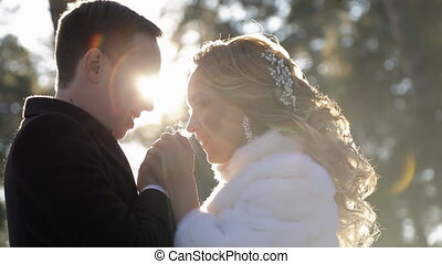 Bride and groom stand in forest holding hands clasped winter.