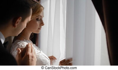 Bride and groom stand near the window