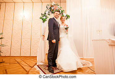 Bride and groom standing at registry office - Full length...