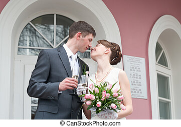 Bride and groom standing near registry office with glasses of champagne and kissing. Caucasians. Young wedding couple
