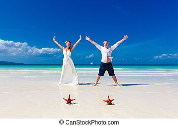 Bride and Groom standing on tropical beach shore with two red starfish in the sand