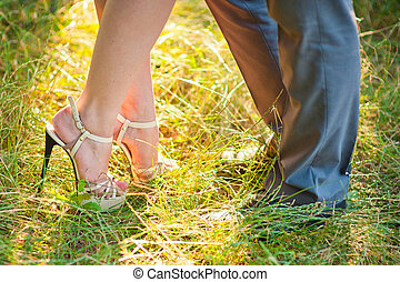 bride and groom stay on green grass