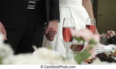 Bride and groom staying and holding hands at wedding dinner