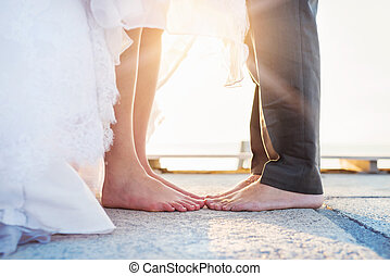 Bride and groom - Feet of a bride and groom standing on the...