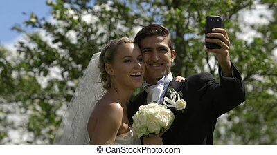 Bride and groom taking a selfie outside on their wedding day