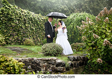 Bride and groom under black umbrella at park