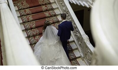 Bride and groom upping the stairs slowmotion