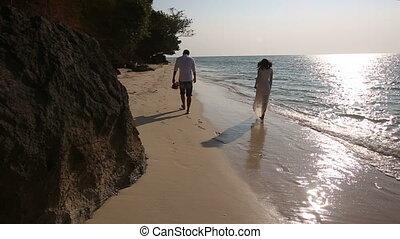 bride and groom walk  along beach barefoot to sun direction