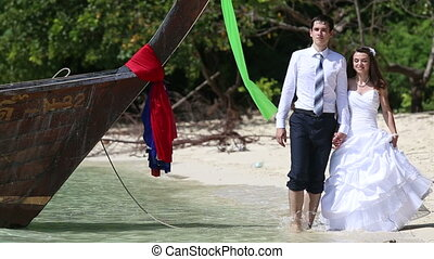 bride and groom walk barefoot past longtail boat along beach