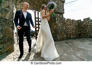 Bride and groom walk dancing into the stone courtyard