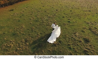 Bride and groom walk in park